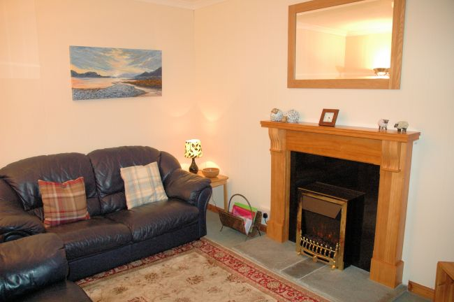 The sitting room in Bruaich Cottage, Lochcarron is cosy with a traditional fireplace and has splendid views.